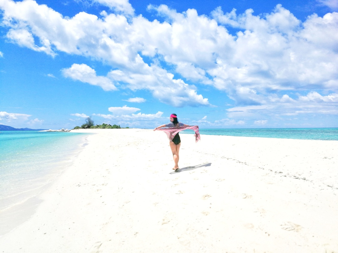 girl walking on a white sand beach