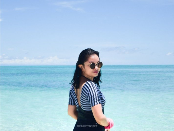 black-haired girl with sunglasses on a crystal lear beach in the philippines